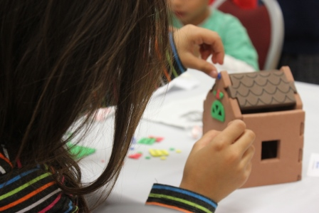 Participant making foam gingerbread houses