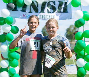 Female competitors smiling at the finish line after the 2015 Kids EXTREME.
