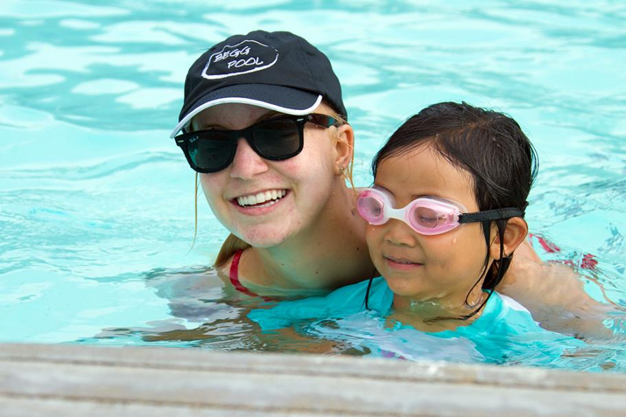 All smiles with swim instructor and student