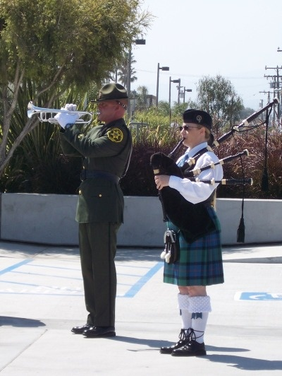 A trumpeter and bagpiper play taps at the close of the Memorial Ceremony
