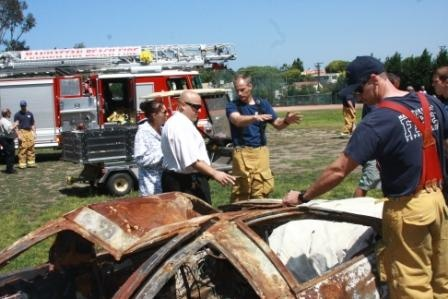 School Resource Officer Kitsios works with Firefighters to stage the mock car crash on the high school field