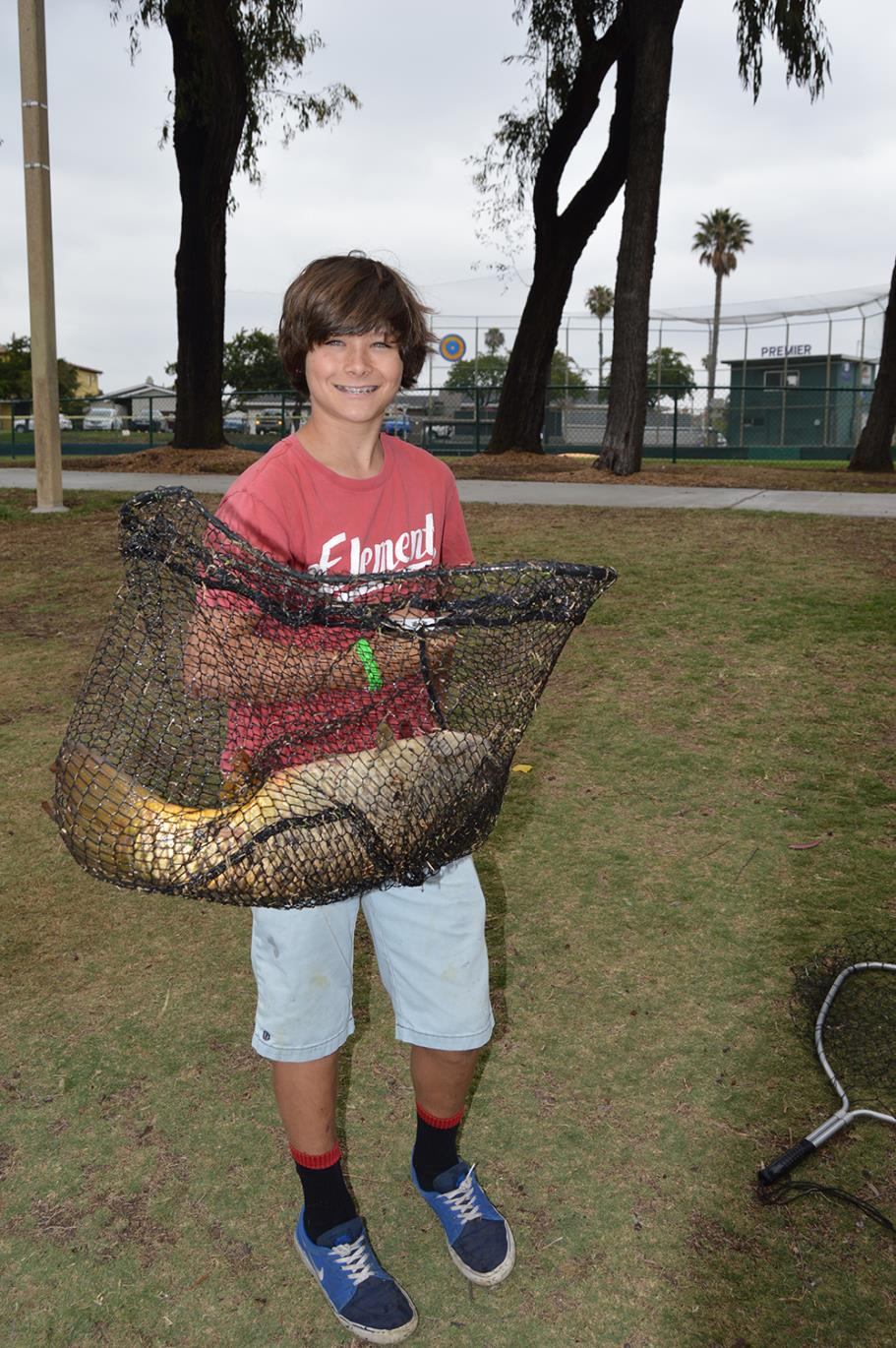 Boy holding a net that has an extremely large carp he caught