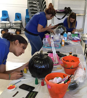Parks and Recreation staff decorating pumpkins