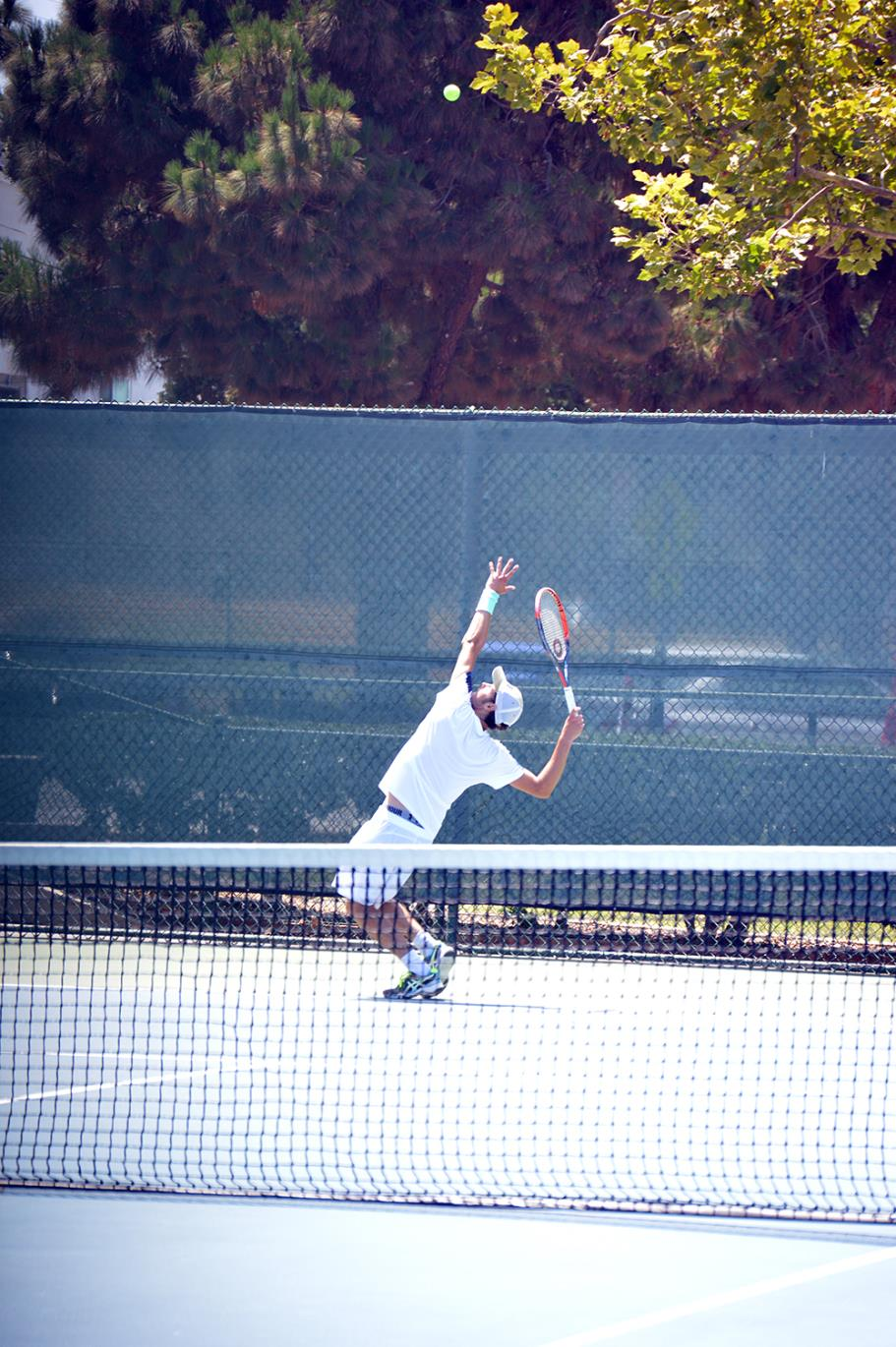 Player serving during a singles match at Live Oak Park Tennis Courts