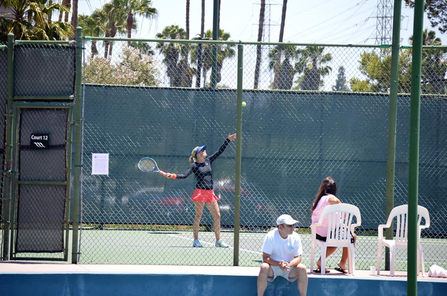 Player serving during the women's finals at the Manhattan Country Club