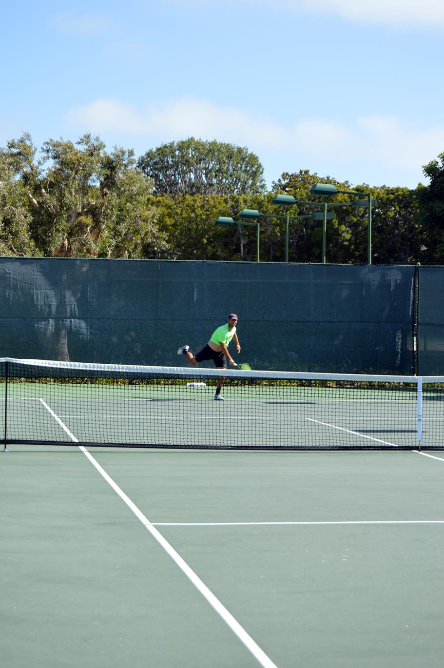 Player serving the ball at Live Oak Park Tennis Courts