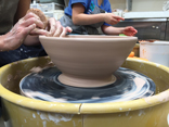 Adult wheel throwing a bowl