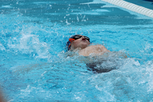 MB Dolphin Swim Team member swimming backstroke in the November 12, 2017 swim meet