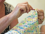 Hands crocheting a blanket