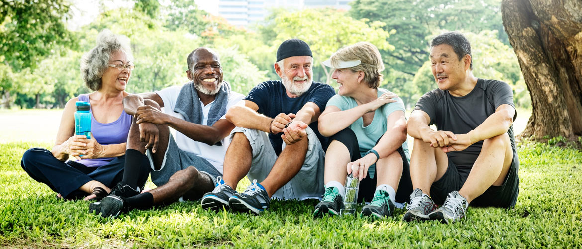 Group of seniors smiling while sitting on grass in a park