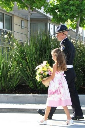 Flowerbearer presents flowers in honor of the three fallen officers
