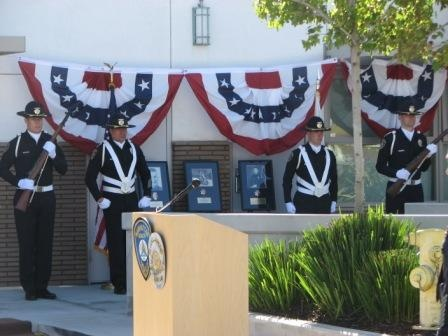 Honor Guard stands beside photos of the Department's three fallen officers