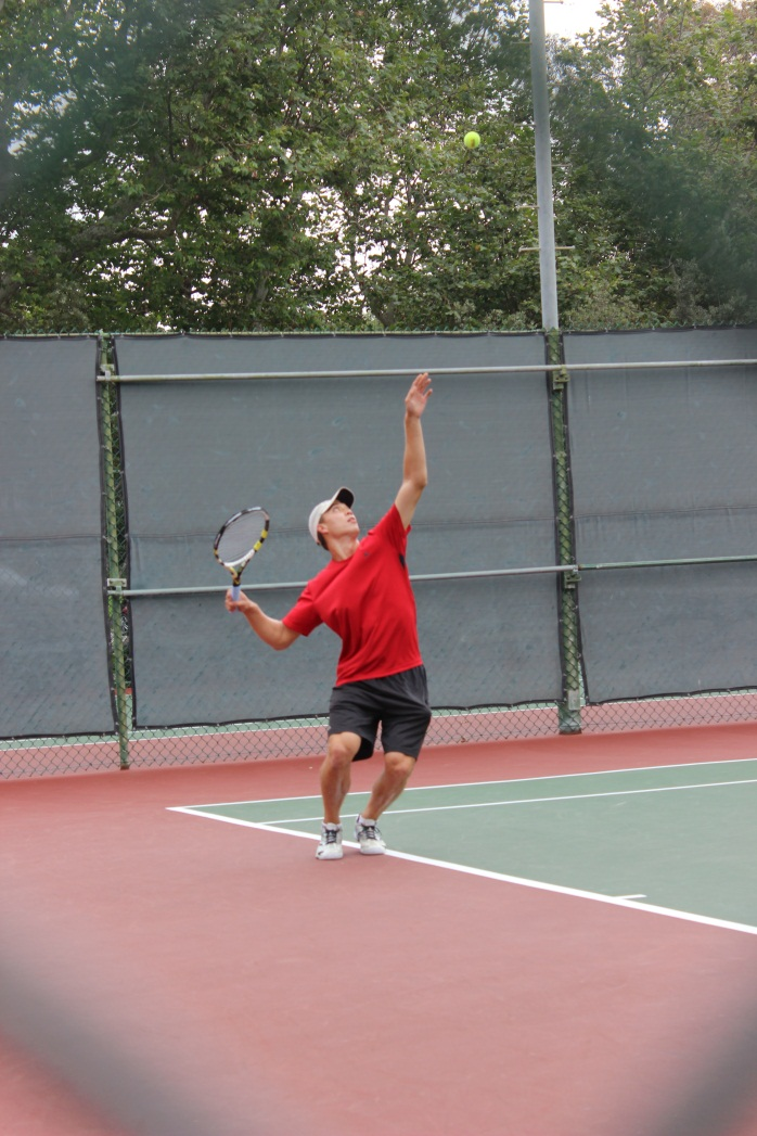 Male player in red shirt serving
