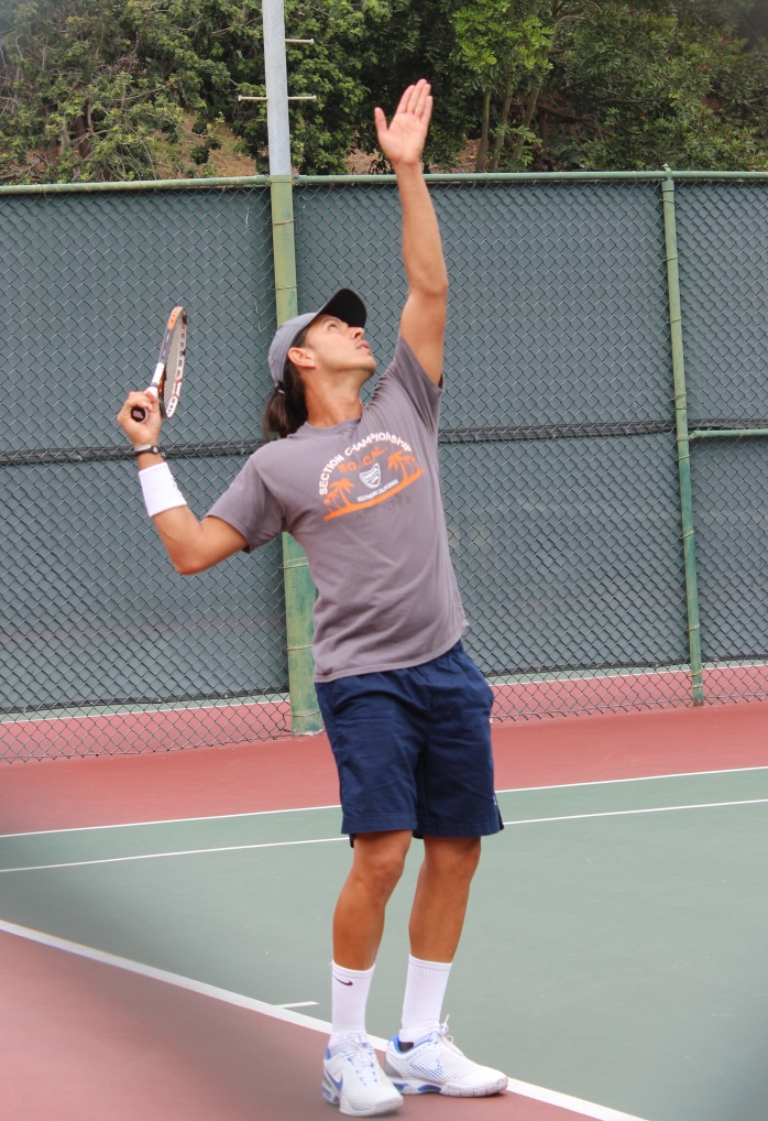 Male player in brown shirt serving