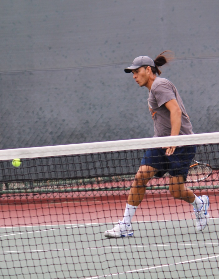 Male player in brown shirt returning forehand