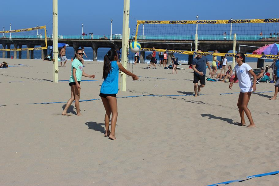 Player bumping the ball during the 2015 Father's Day Beach Volleyball Tournament