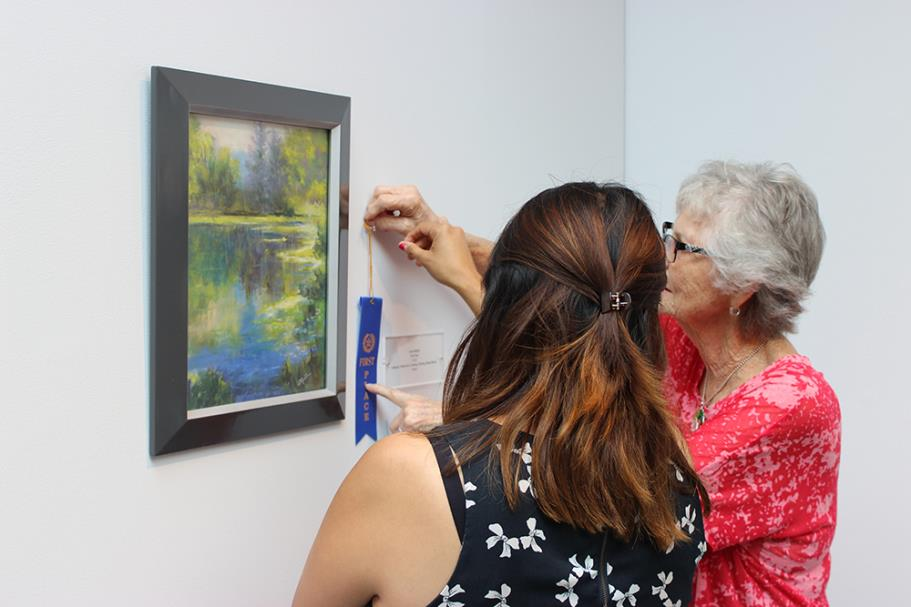 "Linda Melber pinning her first place ribbon on her pastel art piece ""The Pond."""