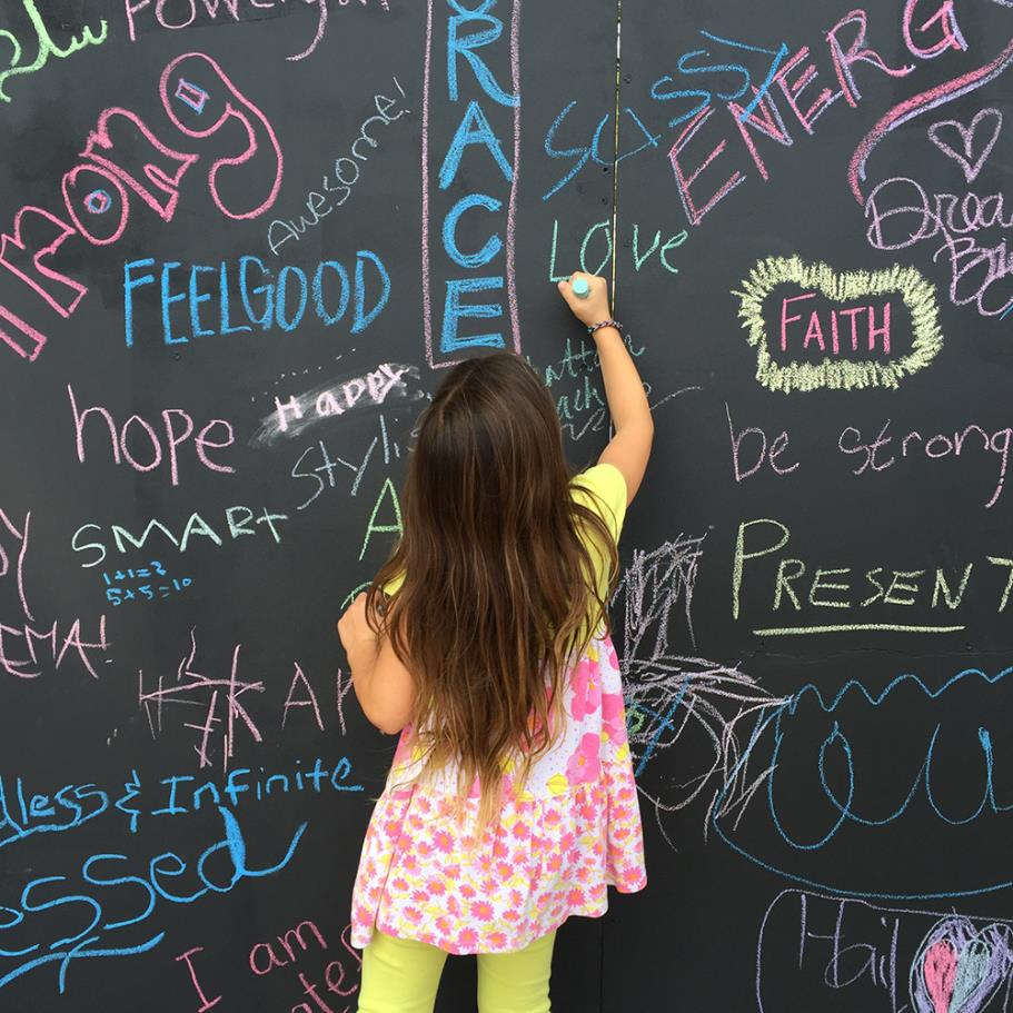 "Girl writing on ""I am.."" chalk wall"