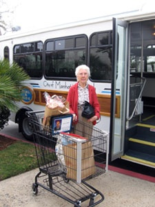 Older adult posing with her shopping cart next to a Dial-A-Ride bus